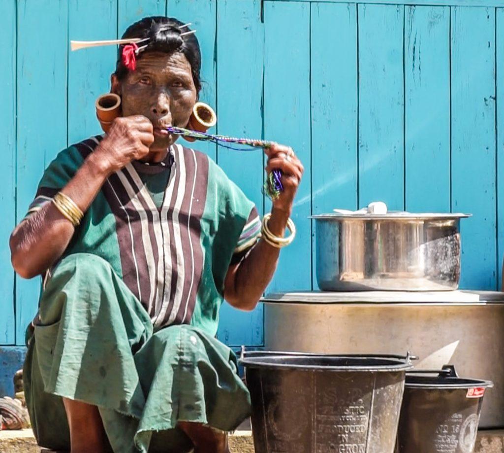 Bà Daw Hang Pai (70 tuổi, người Uppriu) đang dùng miệng để vệ sinh bộ trang sức truyền thống của mình ở công đoạn cuối sau khi đã làm sạch.