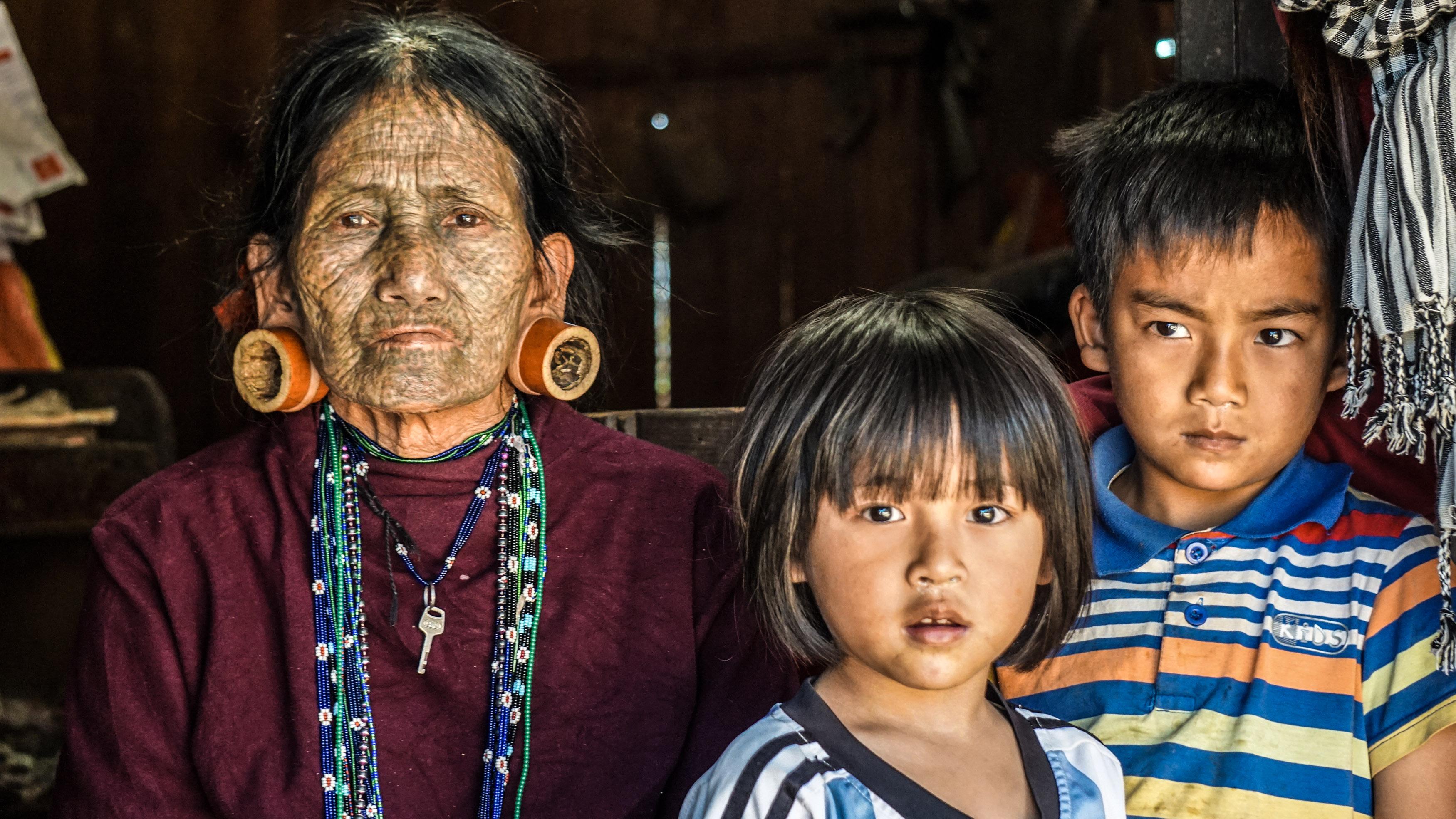 """Bà Aung Seim (73 tuổi, người Uppriu) bên những đứa cháu của mình. Bà kể: """"Khi những đứa cháu của tôi còn nhỏ, chúng thường oà khóc và không chịu cho tôi bồng bế khi trông thấy gương mặt của tôi. Nhưng giờ thì chúng đã quen rồi và rất quấn quýt với tôi""""."""