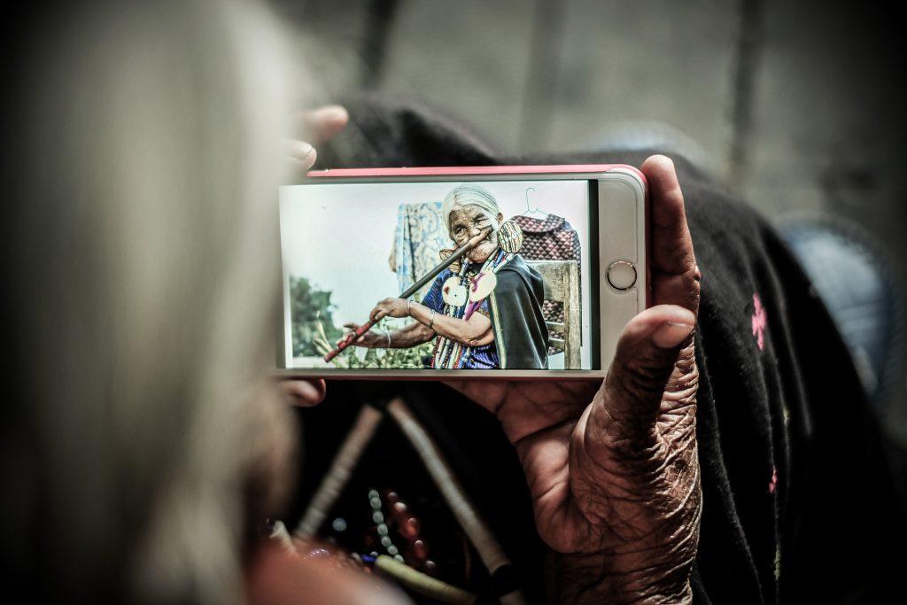 Bà Yaw Shen được một du khách cho xem tấm ảnh nổi tiếng của bà trên thế giới, qua một chiếc điện thoại.
